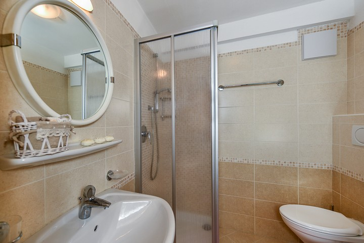 Bathroom with shower, hair dryer and washing machine.